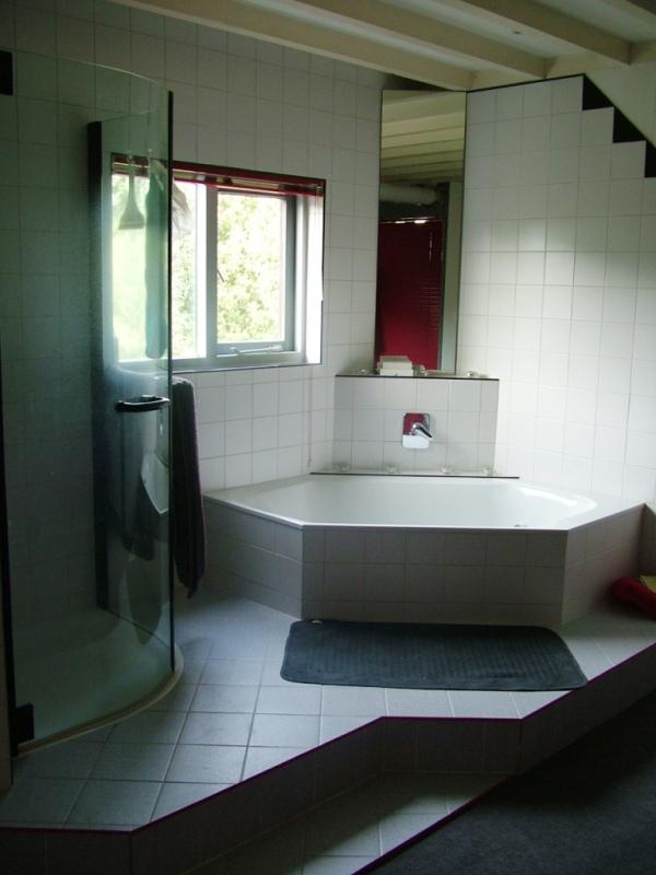 Op zolder is een badkamer met ligbad, douche en wastafel.